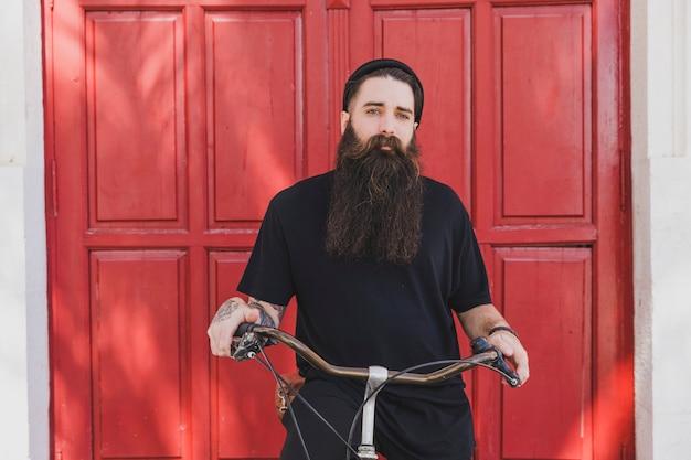 Portret van een lange gebaarde jonge mens die op fiets situeert die camera bekijkt