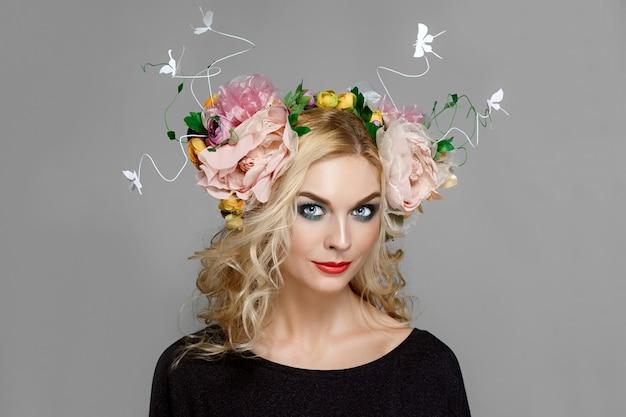 Portret van een lastig meisje met rode lippen en blauwe ogen met kroon van bloemen in blond krullend haar