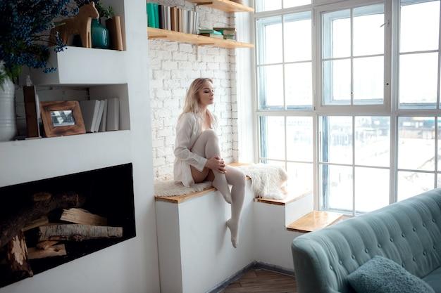 Portret van een leuk, aantrekkelijk, gracieus, dromerig meisje in lingerie met een wit overhemd, genietend van dagdromen op linnen lakens in een huis met een witte lichte kamer