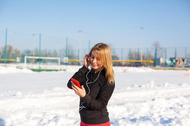 Portret van een leuk blondemeisje die aan muziek luisteren terwijl het lopen onderaan de straat die een rode telefoon in hand houden.
