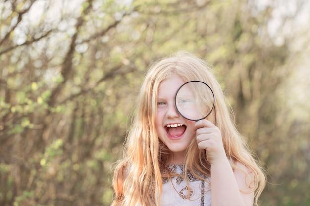 Portret van een leuk jong meisje dat door vergrootglas het park bekijkt