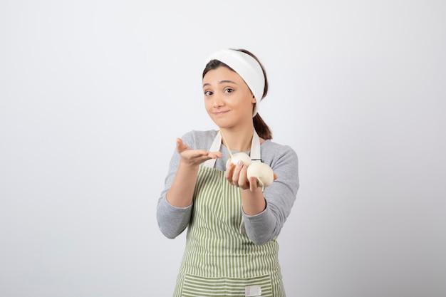 Portret van een leuk jong meisjesmodel dat in schort witte radijsjes houdt.