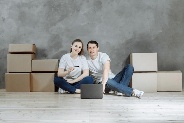 Portret van een leuk jong stel dat een creditcard en laptop gebruikt om meubels voor hun nieuwe huis te kopen.