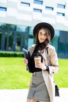 Portret van een leuk jong studentenmeisje op campus met koffie om te gaan. vrouwelijke universiteitsstudent die naar de universiteit gaat