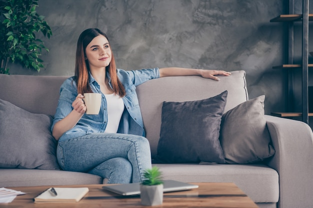 Portret van een leuk, mooi tevreden meisje zit divan met cappuccino-mok