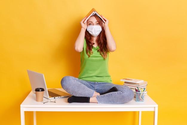 Portret van een leuk uitziende overwerkte meisje met boek als dakhuis op de werkplek zittend op tafel met gekruiste benen