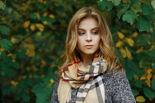 Portret van een leuke aantrekkelijke jonge vrouw in stijlvolle herfstkleren in een park in de buurt van de geelgroene bladeren