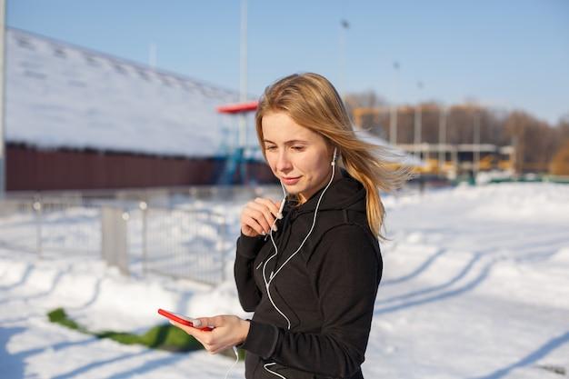 Portret van een leuke blondevrouw die aan muziek luisteren terwijl het lopen onderaan de straat die een rode telefoon in hand houden. er ligt sneeuw rond.