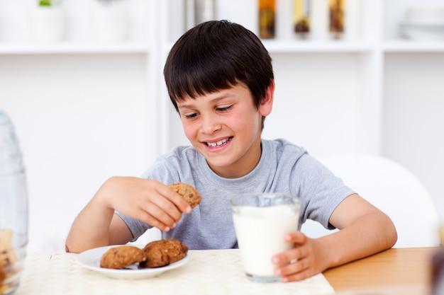 Portret van een leuke jongen die koekjes eet