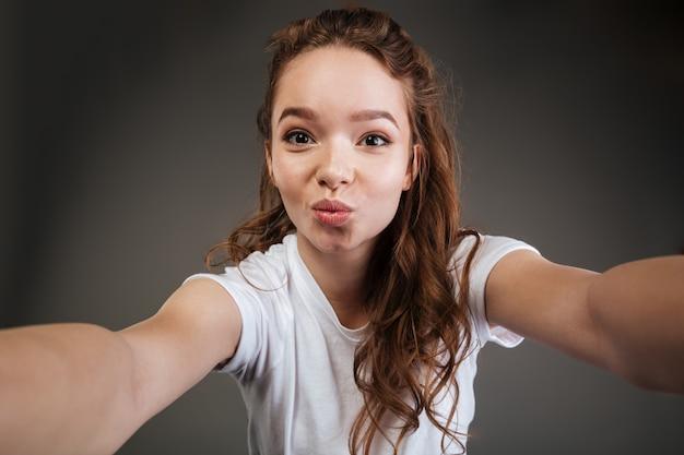 Portret van een leuke mooie tienerholding en het kussen