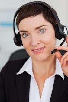 Portret van een leuke secretaresse die met een hoofdtelefoon roept