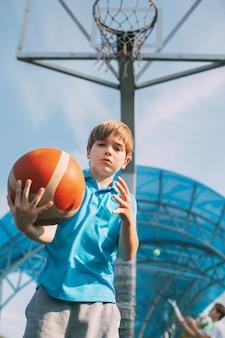 Portret van een leuke speler van het jongensbasketbal die zich met een bal in zijn handen naast het basketbal bevinden