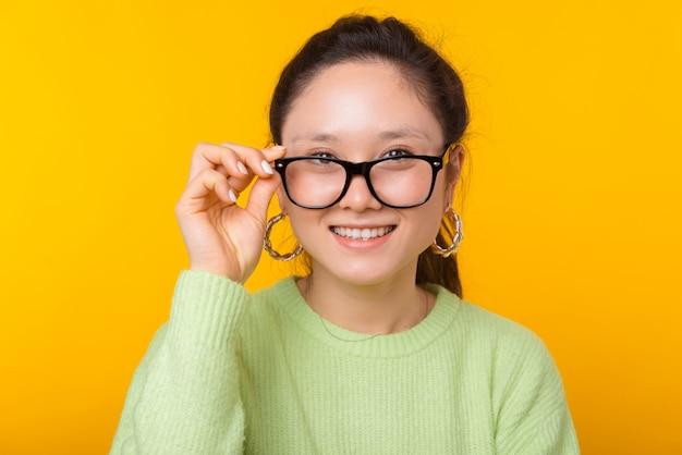 Portret van een leuke vrouw die glazen op geel draagt