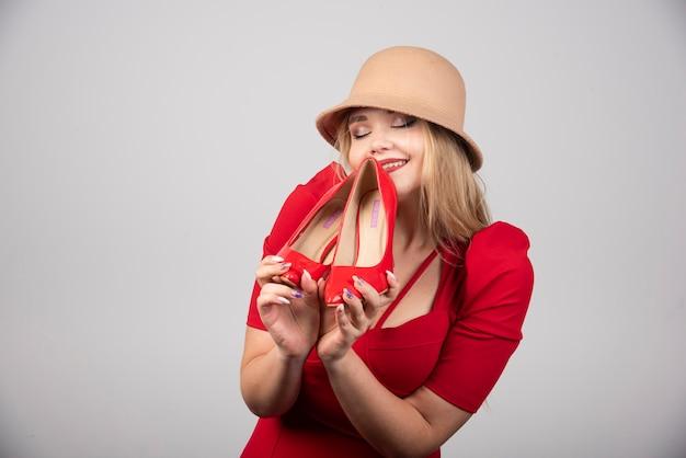 Portret van een leuke vrouw die zich gelukkig voelt met een paar hakken.