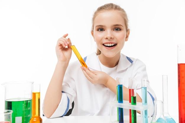 Portret van een lief klein meisje in een witte laboratoriumjas die chemische experimenten maakt met veelkleurige vloeistof in reageerbuizen geïsoleerd over een witte muur