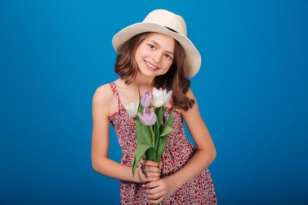 Portret van een lief lachend meisje in een hoed met een boeket bloemen op een blauwe achtergrond
