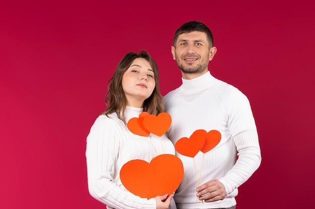 Portret van een liefdevol paar in witte truien op een rode achtergrond.