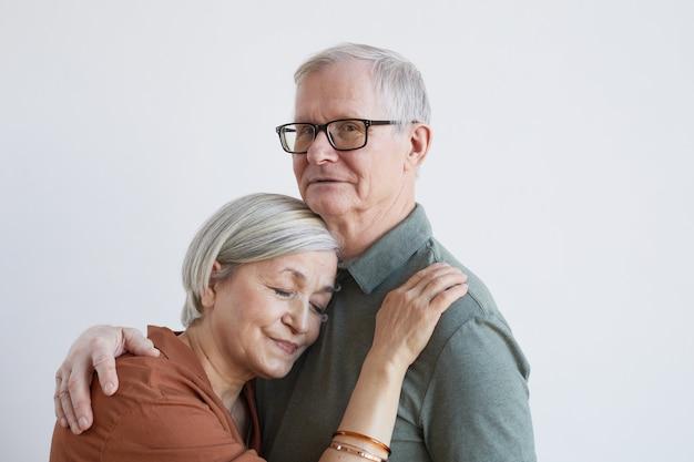 Portret van een liefdevol senior koppel omarmen en kijkend naar de camera terwijl ze tegen een witte achtergrond staan, kopieer ruimte