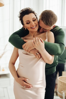 Portret van een liefhebbende echtgenoot die zijn vrolijke zwangere vrouw omhelst in een zijden jurk die de hand op de buik houdt.