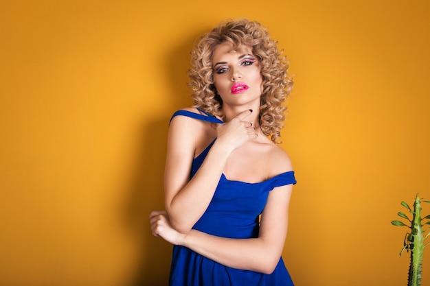 Portret van een luxueuze blonde in een studio op geel