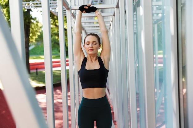 Portret van een magere jonge vrouw die een trainingspak draagt dat aan het trainen is met een horizontale metalen staaf op een sportveld in een groen park