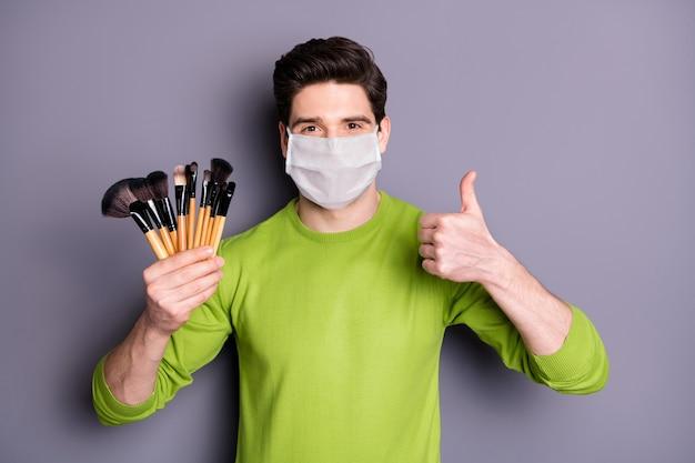 Portret van een make-upartiest die een veiligheidsmasker draagt, kwasten vasthoudt en grieppreventie toont duim omhoog