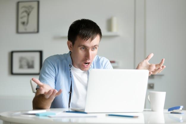 Portret van een man aan het bureau met laptop werken