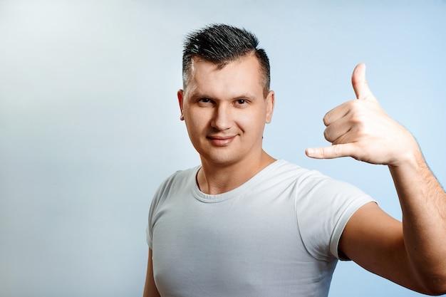 Portret van een man close-up, met een hand om me te bellen, belt u op de telefoon.