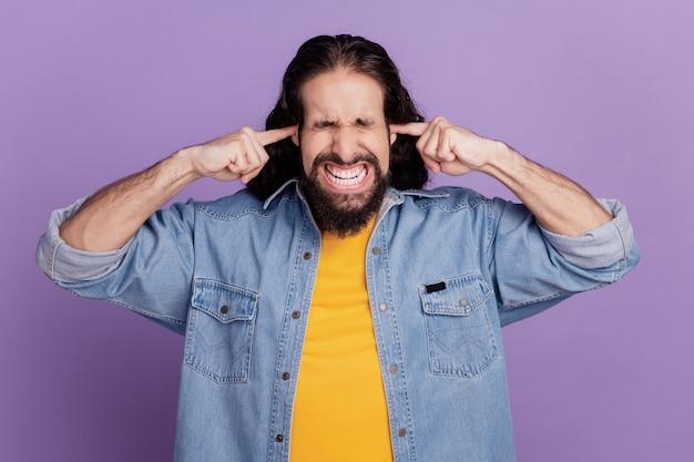 Portret van een man dichte oren knarsetanden geïrriteerde ogen dicht vermijd ruis op paarse muur