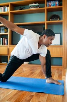 Portret van een man die aan lichaamsbeweging doet terwijl hij thuis blijft