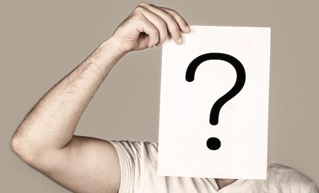 Portret van een man, die achter het verhoorsymbool gluurt. man geïsoleerd. mens een vraag. twijfelachtige man met vraagteken. problemen en oplossingen. vraagteken, symbool. peinzende man