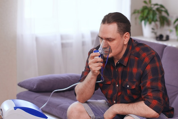 Portret van een man die ademen door een inhalator masker thuis. behandeling van longziekten. kopieer ruimte
