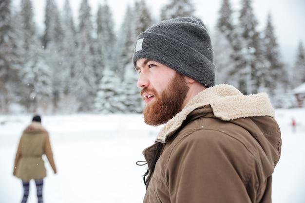 Portret van een man die buiten wegkijkt met sneeuw op backgorund