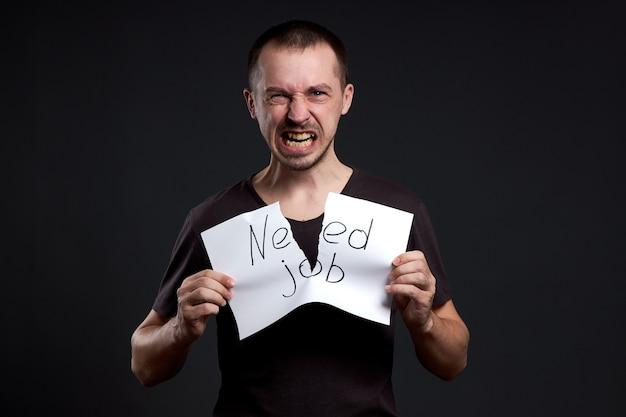 Portret van een man die een inscriptie op papier verscheurt, heeft een baan nodig