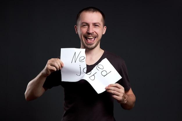 Portret van een man die een inscriptie op papier verscheurt, heeft een baan nodig Premium Foto