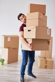Portret van een man die een stapel zware kartonnen dozen draagt