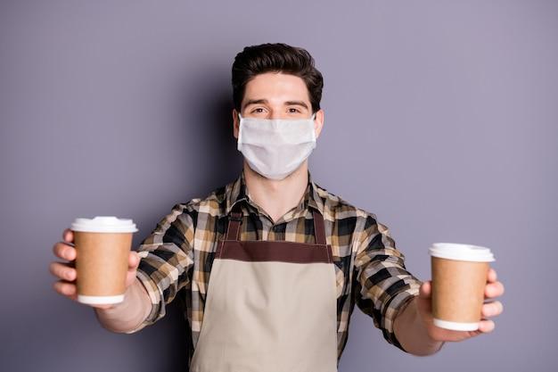 Portret van een man die een veiligheidsmasker draagt en een kopje espresso weggeeft op een grijze achtergrond