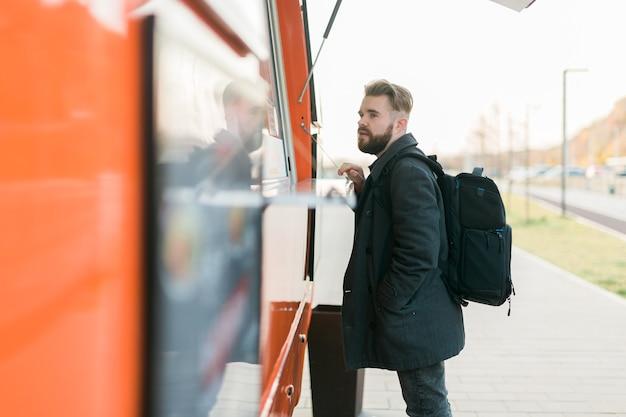 Portret van een man die fastfood kiest in een foodtruck in de voedselindustrie voor straatmaaltijden en streetfood