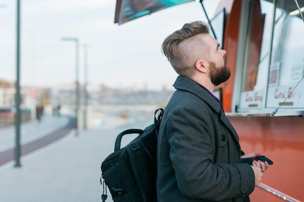 Portret van een man die fastfood kiest in een foodtruck op straat. maaltijd, voedingsindustrie en streetfood concept.