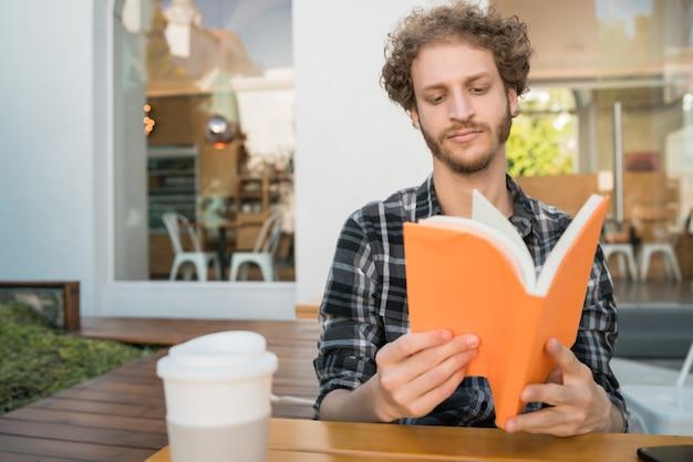 Portret van een man die geniet van vrije tijd en een boek leest terwijl hij buiten zit in de coffeeshop