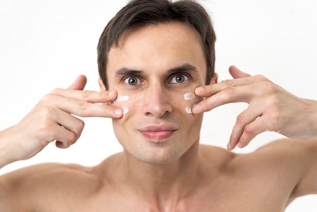 Portret van een man die gezichtslotion toepast