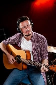 Portret van een man die gitaar speelt en een koptelefoon draagt