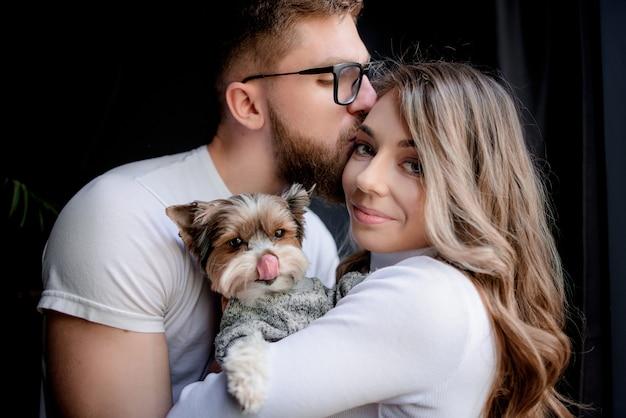 Portret van een man die het voorhoofd van de vrouw kust en grappige puppy op de handen