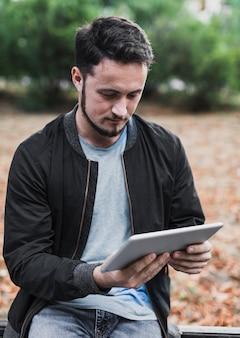 Portret van een man die in een tablet kijkt