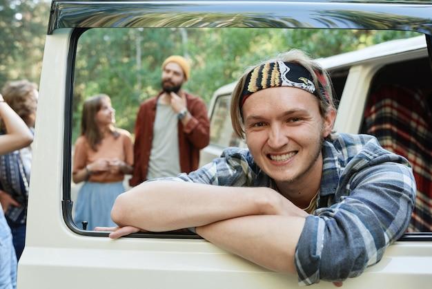 Portret van een man die lacht naar de camera terwijl hij in het busje zit met zijn vrienden op de achtergrond