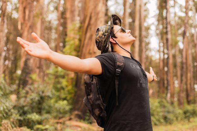 Portret van een man die met open armen geniet van de lucht van de jungle