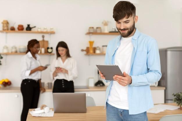Portret van een man die naast zijn collega's werkt