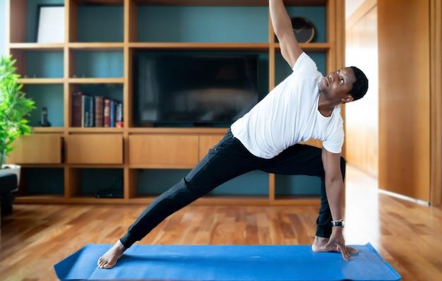 Portret van een man die oefeningen doet terwijl hij thuis blijft. nieuw normaal levensstijlconcept. sportconcept.