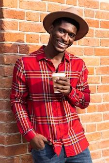 Portret van een man die op een muur leunt en een kopje koffie houdt