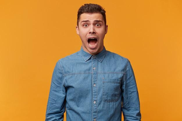 Portret van een man die schreeuwt in paniek, schreeuwend van angst, een luide kreet maakt terwijl hij verbaasd en erg bang is